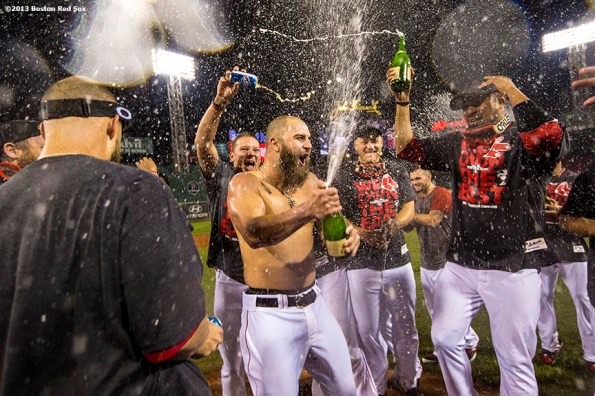 """""""Boston Red Sox first """"Boston Red Sox first baseman Mike Napoli removes his shirt and sprays a bottle of champagne as teammates celebrate on the field after the Red Sox clinched the American League East title with a 6-3 win over the Toronto Blue Jays Friday, September 20, 2013 at Fenway Park."""""""