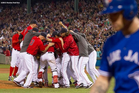 """""""Boston Red Sox teammates celebrate on the field after recording the final out of a 6-3 win over the Toronto Blue Jays to clinch the American League East title at Fenway Park Friday, September 20, 2013."""""""