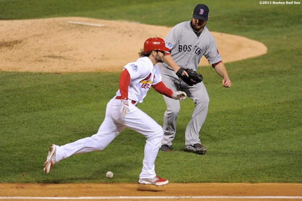 """""""Boston Red Sox pitcher Jon Lester fields a bunt from shortstop Pete Kozma during the third inning of game five of the 2013 World Series against the St. Louis Cardinals Monday, October 28, 2013 at Busch Stadium in St. Louis, Missouri."""""""
