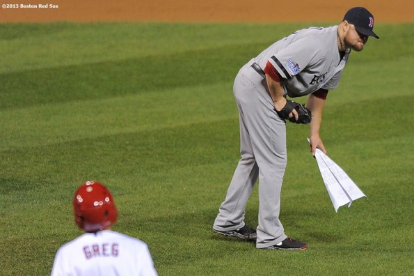 """""""Boston Red Sox pitcher Jon Lester picks up a paper airplane thrown on the field by a fan during the seventh inning of game five of the 2013 World Series against the St. Louis Cardinals Monday, October 28, 2013 at Busch Stadium in St. Louis, Missouri."""""""