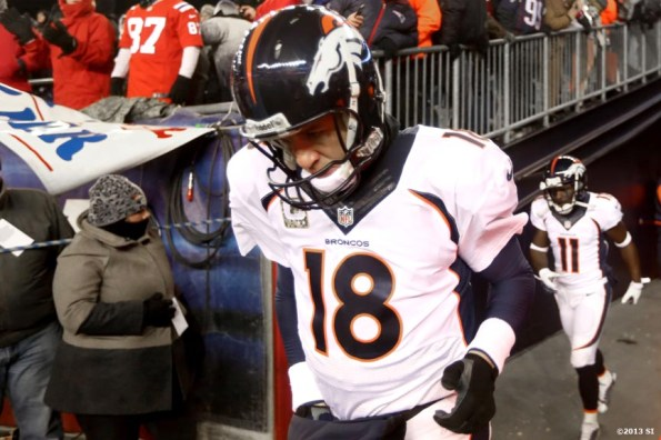 """""""Denver Broncos quarterback Peyton Manning walks onto the field before a game against the New England Patriots Sunday, November 24, 2013 at Gilette Stadium in Foxborough, Massachusetts."""""""