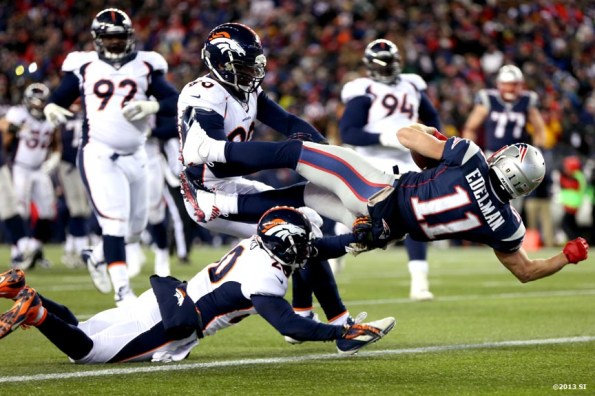 """""""New England Patriots wide receiver Julian Edelman dives toward the end zone as he scores a touchdown during a game against the Denver Broncos Sunday, November 24, 2013 at Gillette Stadium in Foxborough, Massachusetts."""""""
