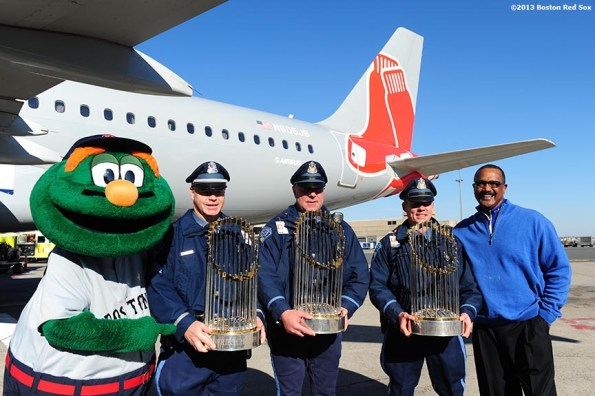 """""""Boston Red Sox mascot Wally the Green Monster, members of the Boston Police Department, and former Red Sox left fielder Jim Rice pose for a photograph on the runway during a Boston Red Sox visit to jetBlue Airways terminal at Logan Airport in Boston, Massachusetts Thursday, November 14, 2013 to unveil a 2013 World Series Championship banner."""""""