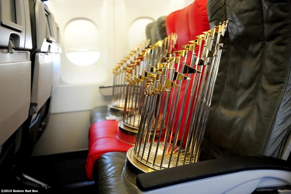 """""""The 2004, 2007, and 2013 World Series trophies are displayed across an aisle of seats on a jetBlue airplane during a Boston Red Sox visit to jetBlue Airways terminal at Logan Airport in Boston, Massachusetts Thursday, November 14, 2013 to unveil a 2013 World Series Championship banner."""""""