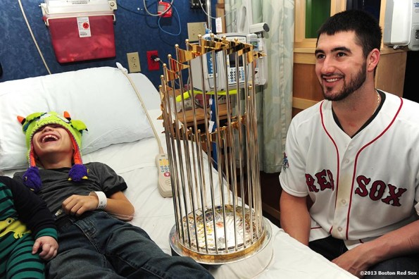 """""""Boston Red Sox pitcher Brandon Workman shares a laugh with a patient as he shows him the World Series trophy during a visit to The Jimmy Fund at Dana-Farber Cancer Institute in Boston, Massachusetts Friday, December 13, 2013 as part of the Red Sox Holiday Caravan to various locations throughout Boston."""""""