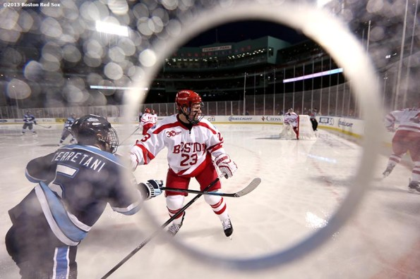 """""""Game action shown through a photographer's hole during a game between University of Maine and Boston University at Frozen Fenway Saturday, January 11, 2014 at Fenway Park in Boston, Massachusetts."""""""