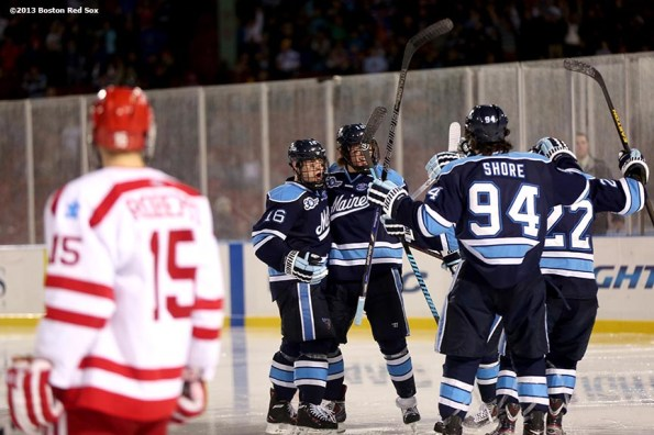 """""""University of Maine players celebrate after scoring a goal against Boston University Saturday, January 11, 2014 at Fenway Park in Boston, Massachusetts."""""""