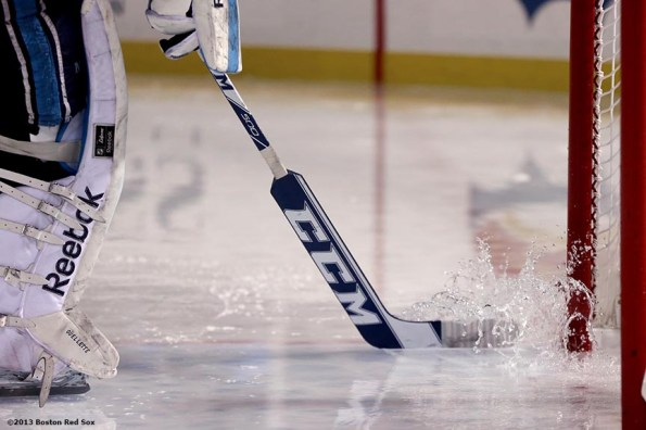"""""""A goalie pushes water off the ice with his stick after a rain delay during a game between University of Maine and Boston University at Frozen Fenway Saturday, January 11, 2014 at Fenway Park in Boston, Massachusetts."""""""