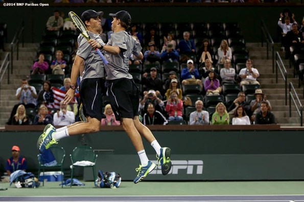 """""""Bob and Mike Bryan chest bump each other after winning their third round doubles match Tuesday, March 11, 2014 in Indian Wells, California."""""""