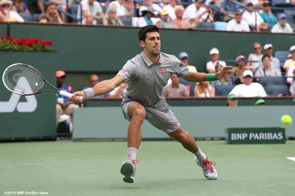 """""""Novak Djokovic lunges for a forehand against Alejandro Gonzalez in a third round match at the 2014 BNP Paribas Open Tuesday, March 11, 2014 in Indian Wells, California."""""""