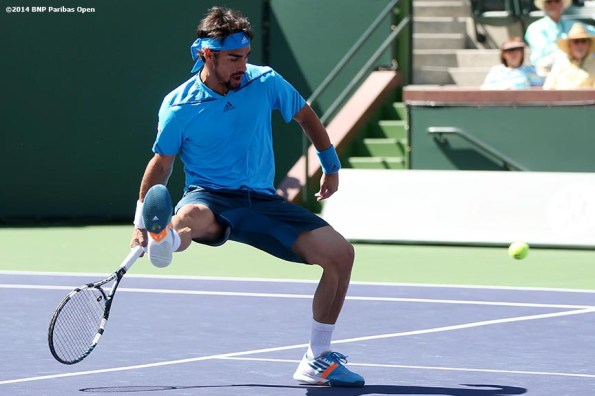 """""""Fabio Fognini hits a shot beween his legs during a fourth round match against Alexandr Dolgopolov at the 2014 BNP Paribas Open Wednesday, March 12, 2014 in Indian Wells, California."""""""