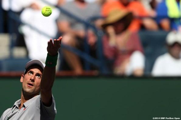 """Novak Djokovic eyes a serve against Julien Benneteau in the quarterfinal of the 2014 BNP Paribas Open Friday, March 14, 2014 in Indian Wells, California."""