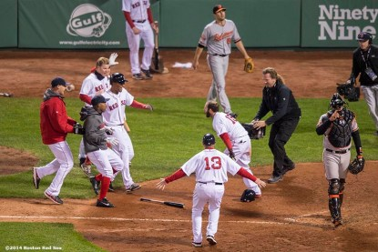 """""""Members of the Boston Red Sox celebrate after second baseman Dustin Pedroia scored the winning run on a throwing error in the ninth inning of a game against the Baltimore Orioles at Fenway Park Sunday, April 20, 2014. The Red Sox won 6-5."""""""