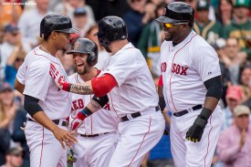 """""""Boston Red Sox left fielder Jonny Gomes celebrates with shortstop Xander Bogaerts, second baseman Dustin Pedroia, and designated hitter David Ortiz after hitting a grand slam home run during the first inning of a game against the Oakland Athletics Saturday, May 4, 2014 at Fenway Park in Boston, Massachusetts."""""""