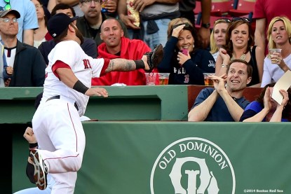 """""""Boston Red Sox first baseman Mike Napoli reaches into the stands to catch a foul ball during the first inning of a game against the Detroit Tigers at Fenway Park in Boston, Massachusetts Saturday, May 17, 2014."""""""