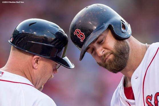 """""""Boston Red Sox first baseman Mike Napoli bumps helmets with first base coach Arnie Beyeler after hitting a single during the eighth inning of a game against the Cleveland Indians Saturday, June 14, 2014 at Fenway Park in Boston, Massachusetts."""""""