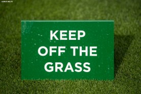 """A sign that reads 'Keep Off The Grass' is shown at the All England Lawn and Tennis Club in London, England Sunday, June 22, 2014 during the 2014 Championships Wimbledon."""""""
