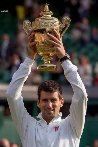 """""""Novak Djokovic poses with the Champion's trophy after defeating Roger Federer in the gentlemen's singles final at the All England Lawn and Tennis Club in London, England Sunday, July 6, 2014 during the 2014 Championships Wimbledon."""""""