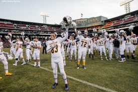 """""""Members of the Xaverian Brothers High School football team raise their helmets before a game against St. John's Preparatory School at Fenway Park in Boston, Massachusetts Wednesday, November 25, 2015."""""""