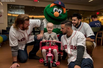 """""""Boston Red Sox pitcher Robbie Ross Jr., infielder Deven Marrero, pitcher Noe Ramirez and mascot Wally the Green Monster greet a patient at Dana Farber Cancer Institute during the Holiday Caravan in Boston, Massachusetts Wednesday, December 9, 2015."""""""