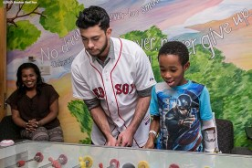 """""""Boston Red Sox pitcher Noe Ramirez plays foozball with patient at Boston Medical Center during the Holiday Caravan in Boston, Massachusetts Friday, December 10, 2015."""""""