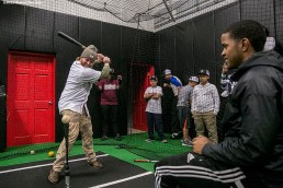 """""""Boston Red Sox pitcher Robbie Ross Jr. takes swings in the cage as kids watch at the Base during the Holiday Caravan in Boston, Massachusetts Friday, December 10, 2015."""""""