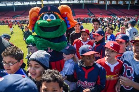"""""""Fans play in the outfield with Boston Red Sox mascot Tessie during Little League Opening Day at Fenway Park in Boston, Massachusetts Saturday, April 9, 2016."""""""