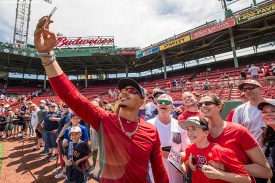 BOSTON, MA - MAY 14: Mookie Betts #50 of the Boston Red Sox takes a selfie photograph with fans during on field photo day before a game against the Houston Astros on May 14, 2016 at Fenway Park in Boston, Massachusetts. (Photo by Billie Weiss/Boston Red Sox/Getty Images) *** Local Caption *** Mookie Betts