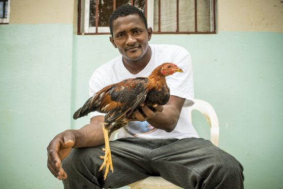 July 21, 2017, Boston, MA: A local man poses for a photograph with his chicken in El Mamón during the 2017 Lindos Sueños trip in the Dominican Republic Friday, July 21, 2017. (Photo by Billie Weiss/Boston Red Sox)