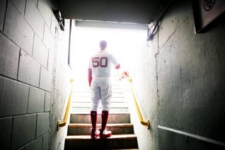 BOSTON, MA - APRIL 14: Mookie Betts #50 of the Boston Red Sox walks stands in the dugout as the National Anthem is played before a game against the Baltimore Orioles on April 14, 2018 at Fenway Park in Boston, Massachusetts. (Photo by Billie Weiss/Boston Red Sox/Getty Images) *** Local Caption *** Mookie Betts