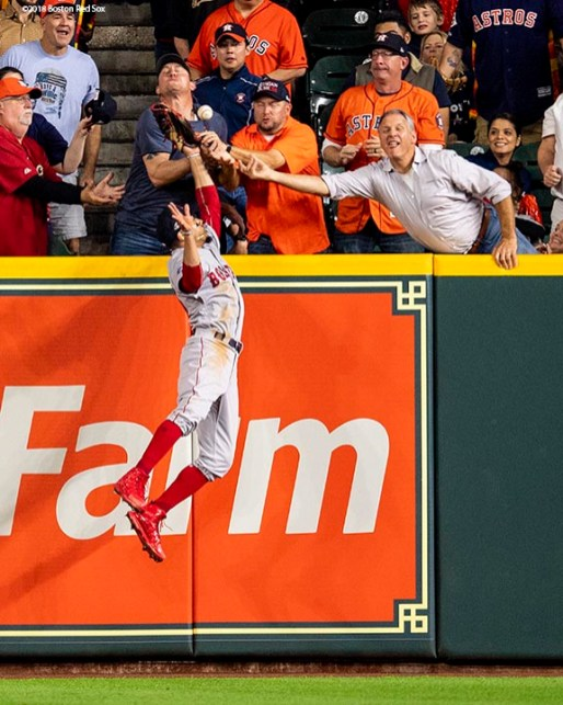 HOUSTON, TX - OCTOBER 17: A fan interferes with Mookie Betts #50 of the Boston Red Sox as he attempts to catch a ball hit by Jose Altuve #27 of the Houston Astros (not pictured) in the first inning during Game Four of the American League Championship Series at Minute Maid Park on October 17, 2018 in Houston, Texas. (Photo by Billie Weiss/Boston Red Sox/Getty Images) *** Local Caption *** Jose Altuve; Mookie Betts