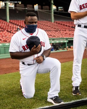 BOSTON, MA - JULY 24: Third base coach Carlos Febles of the Boston Red Sox kneels during the National Anthem during a pre-game ceremony before the Opening Day game against the Baltimore Orioles on July 24, 2020 at Fenway Park in Boston, Massachusetts. The 2020 season had been postponed since March due to the COVID-19 pandemic. (Photo by Billie Weiss/Boston Red Sox/Getty Images) *** Local Caption *** Carlos Febles