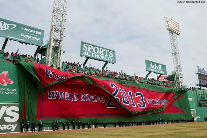 """The 2013 World Series championship banner is dropped over the Green Monster during the Boston Red Sox World Series ring ceremony at the 2014 season home opener Friday, April 4, 2014 at Fenway Park in Boston, Massachusetts."""