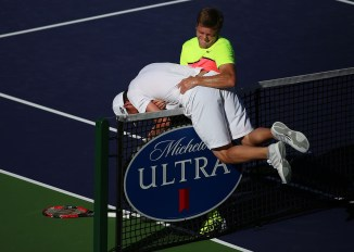 """Ryan Harrison helps his opponent, Mardy Fish, after Fish flipped over the net during their match inside Stadium 1 at the Indian Wells Tennis Garden in Indian Wells, California Tuesday, March 12, 2015."""