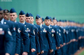"""Members of the Hanscom Air Force Base serve as a flag bearers before the American flag is dropped over the Green Monster in honor of Patriot's Day before a game between the Boston Red Sox and the Baltimore Orioles at Fenway Park in Boston, Massachusetts Monday, April 20, 2015."""