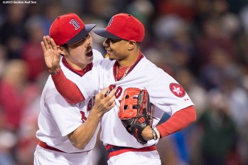 """Boston Red Sox pitcher Koji Uehara high fives center fielder Mookie Betts after defeating theTampa Bay Rays at Fenway Park in Boston, Massachusetts Tuesday, May 5, 2015."""