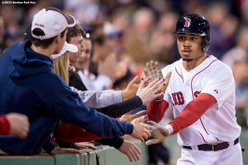 """""""Boston Red Sox center fielder Mookie Betts high fives fans after scoring during the seventh inning of a game against the Texas Rangers at Fenway Park in Boston, Massachusetts Saturday, May 23, 2015."""""""