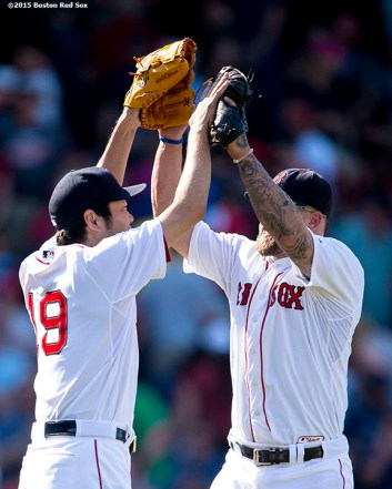 """Boston Red Sox pitcher Koji Uehara and first baseman Mike Napoli high five after defeating the Los Angeles Angels of Anaheim at Fenway Park in Boston, Massachusetts Sunday, May 24, 2015."""