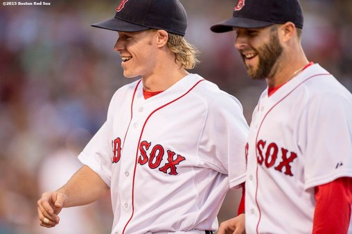 """Boston Red Sox first baseman Brock Holt and second baseman Dustin Pedroia react during the fourth inning of a game against the Baltimore Orioles at Fenway Park in Boston, Massachusetts Wednesday, June 24, 2015."""