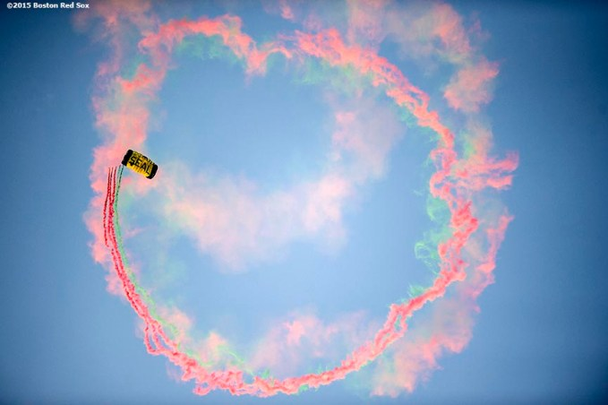 """A US Navy SEALS sprays smoke as he parachutes into Fenway Park before a game between the Boston Red Sox and the Houston Astros at Fenway Park in Boston, Massachusetts Friday, July 3, 2015."""