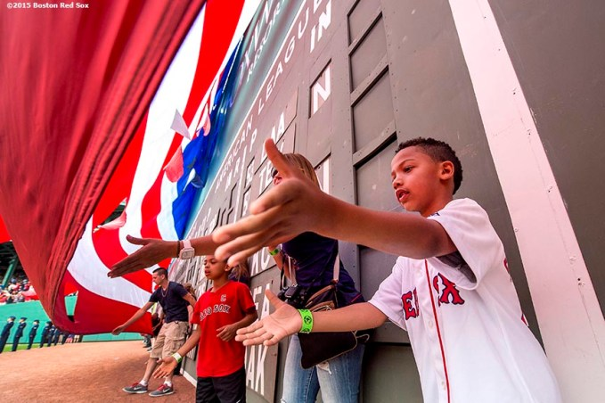 """A boy reaches out to catch the American flag as it is dropped over the Green Monster before a game between the Boston Red Sox and the Houston Astros at Fenway Park in Boston, Massachusetts Saturday, July 4, 2015."""