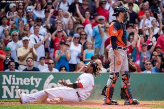"""Boston Red Sox left fielder Hanley Ramirez slides into home plate as he scores during the sixth inning of a game against the Houston Astros at Fenway Park in Boston, Massachusetts Sunday, July 5, 2015."""