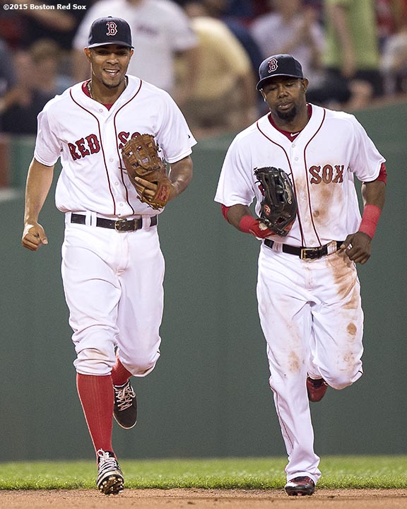 """Boston Red Sox shortstop Xander Bogaerts and left fielder Alejandro De Aza laugh during the eighth inning of a game against the Miami Marlins at Fenway Park in Boston, Massachusetts Wednesday, July 8, 2015."""