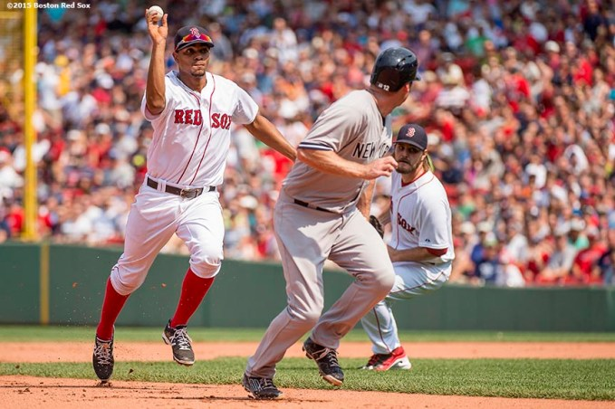 """Boston Red Sox shortstop Xander Bogaerts throws during a run-down during a game against the New York Yankees at Fenway Park in Boston, Massachusetts Sunday, July 12, 2015. """