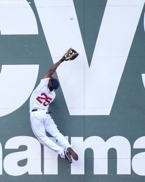 """Boston Red Sox left fielder Jackie Bradley Jr. leaps as he attempts to catch a fly ball during the seventh inning of a game against the Seattle Mariners at Fenway Park in Boston, Massachusetts Sunday, August 16, 2015."""
