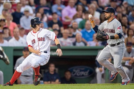 """""""Boston Red Sox second baseman Brock Holt gets caught in a run down by third baseman Mike Aviles during the first inning of a game against the Cleveland Indians at Fenway Park in Boston, Massachusetts Tuesday, August 18, 2015."""""""