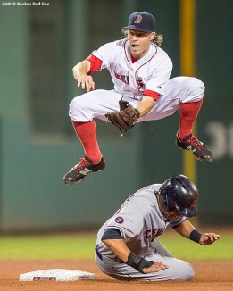 """Boston Red Sox second baseman Brock Holt turns a double play during the fourth inning of a game against the Cleveland Indians at Fenway Park in Boston, Massachusetts Wednesday, August 19, 2015."""