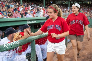 """Jimmy Fund patients high five players before a game between the Boston Red Sox and the Cleveland Indians at Fenway Park in Boston, Massachusetts Wednesday, August 19, 2015."""
