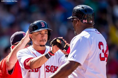 """Boston Red Sox center fielder Mookie Betts high fives designated hitter David Ortiz after scoring during the second inning of a game against the Philadelphia Phillies at Fenway Park in Boston, Massachusetts Sunday, September 6, 2015."""
