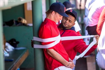 """Boston Red Sox pitcher Henry Owens is taped to a pole in the dugout by third baseman Pablo Sandoval during the third inning of a game against the Philadelphia Phillies at Fenway Park in Boston, Massachusetts Sunday, September 6, 2015."""